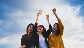 Happy group of asia girl friends enjoy laughing and cheerful toast sparkling wine glass at rooftop party,Holiday celebration royalty free stock images