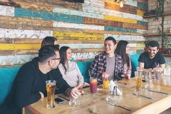 Happy group of best friends having fun drinking beer while waiting food order at restaurant. – young people enjoying time together laughing at jokes and stock image