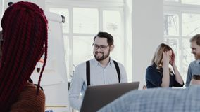 Happy group of business people listen to male leader speaking at comfortable office workplace slow motion RED EPIC. Smiling relaxed corporate partners stock video footage