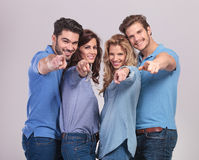 Happy group of casual people pointing fingers. To the camera on grey background Royalty Free Stock Photos