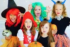 Happy group of children in costumes during Halloween party. Playing around the table with pumpkins and bottle of potion Stock Images