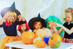 Happy group of children in costumes preparing for Halloween. Playing around the table with pumpkins and bottle of potion Stock Photo