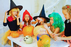 Happy group of children in costumes preparing for Halloween. Playing around the table with pumpkins and bottle of potion Royalty Free Stock Photography