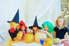 Happy group of children in costumes preparing for Halloween. Playing around the table with pumpkins and bottle of potion Royalty Free Stock Image