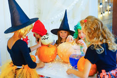 Happy group of children in costumes preparing for Halloween. Playing around the table with pumpkins and bottle of potion Stock Photography