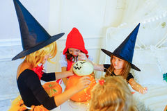 Happy group of children in costumes preparing for Halloween. Playing around the table with pumpkins and bottle of potion Stock Image