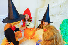 Happy group of children in costumes preparing for Halloween. Playing around the table with pumpkins and bottle of potion Royalty Free Stock Photo