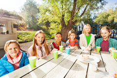 Happy group of children sitting at table outside royalty free stock photo