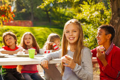 Happy group of children sitting at wooden table Stock Photos