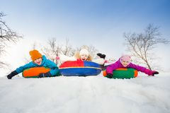 Happy group of children slide on tubes in a row Royalty Free Stock Images