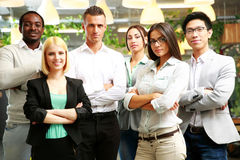Happy group of co-workers with arms folded. Standing in office Stock Image