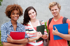 Happy group of college students. Happy group of students holding notebooks outdoors Stock Photo