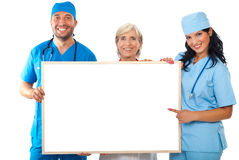 Happy group of doctors holding placard. Happy group of doctors holding a blank placard and a doctor woman pointing to copy space banner isolated on white Stock Images