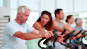 Happy group doing a spinning class with trainer smiling at camera Royalty Free Stock Photos