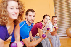 Happy group with dumbbells. Happy group exercising together with dumbbells in fitness center Stock Image