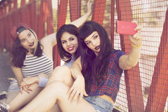 Happy group of female friends taking a self portrait. Group of teenage friends taking a self portrait with mobile phone Royalty Free Stock Image
