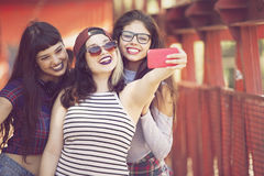 Happy group of female friends taking a self portrait. Group of teenage friends taking a self portrait with mobile phone Royalty Free Stock Photo