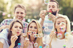 Happy group of friends blowing bubbles outdoors Royalty Free Stock Images