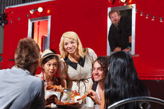 Happy People Eating By Canteen. Happy group of friends eating out by food truck Royalty Free Stock Photo