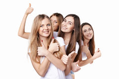 Happy group of friends gesturing thumbs up. Happy group of friends girls gesturing thumbs up, over white background Stock Images
