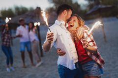 Happy group of friends lighting sparklers and enjoying freedom. At beach during sunset royalty free stock photo