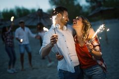 Happy group of friends lighting sparklers and enjoying freedom. At beach during sunset Stock Images
