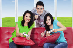 Happy group of friends play video games. Portrait of group of teenager playing video games with joystick while sitting on the couch at sofa Stock Images