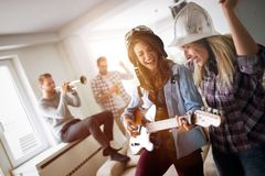 Happy group of friends playing instruments and partying. Happy group of fun and cheerful friends playing instruments and partying Stock Image