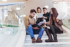 Happy group of friends sitting on the stairs in the school Stock Photography