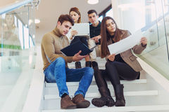 Happy group of friends sitting on the stairs in the school Royalty Free Stock Photo