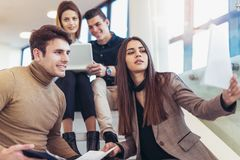 Happy group of friends sitting on the stairs in the school Royalty Free Stock Images