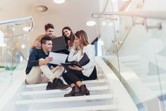 Happy group of friends sitting on the stairs in the school Royalty Free Stock Image