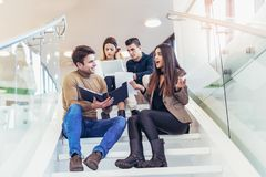 Happy group of friends sitting on the stairs in the school Royalty Free Stock Photos