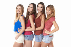 Happy group of friends standing in a row. Happy group of friends girls standing in a row hugging, over white background Royalty Free Stock Photography