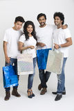 Happy group of friends standing with shopping bags Stock Photos