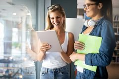 Happy group of friends studying and talking together at university royalty free stock image