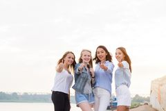 Happy group of friends with thumbs up stock images