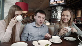 Happy group of friends Two young women and a man chatting, having drinks in city coffee shop cafe, stock footage