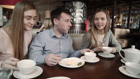 Happy group of friends Two young women and a man chatting, having drinks in city coffee shop cafe, stock video footage