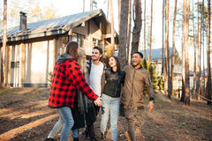 Happy group of friends walking outdoors in the forest. Royalty Free Stock Image