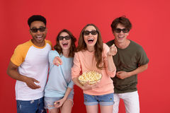 Happy group of friends watching film eating popcorn. Royalty Free Stock Photography