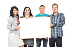 Happy group holding blank banner. Happy group of four people holding a blank banner and one woman pointing to copy space isolated on white background Stock Photo
