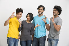 Happy group of Indian young friends showing satisfied sign Royalty Free Stock Image
