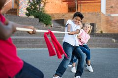 Children playing tug of war. Happy group of kids playing tug of war outdoor. Young boys and girls as a team in tug-of-war outside the school. Group of happy Stock Image