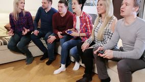 Friends play video games together. Happy group of male friends playing video games at home stock video footage
