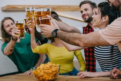 happy group of multicultural friends clinking beer bottles and watching soccer match royalty free stock image