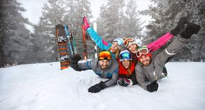 Happy group of skiers lying on snow. With raised hands Stock Photos