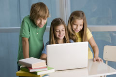 Happy group of students. With computer at school Royalty Free Stock Images