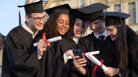 Happy group of students on graduation day laughing at something on mobile phone.