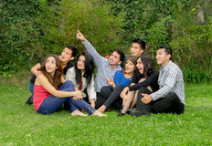Happy group of students sitting at the park. Talking Royalty Free Stock Photos